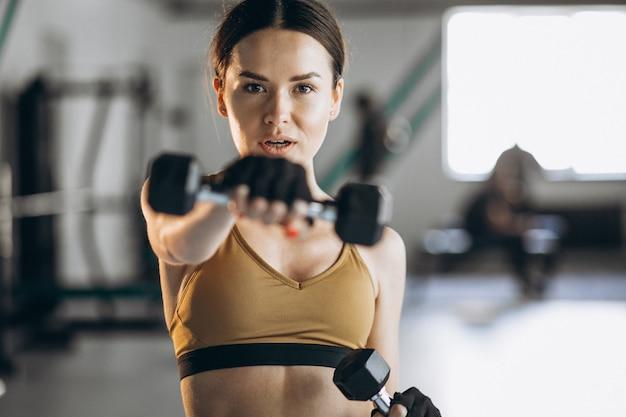 Mujer joven atractiva que ejercita con pesas en el gimnasio