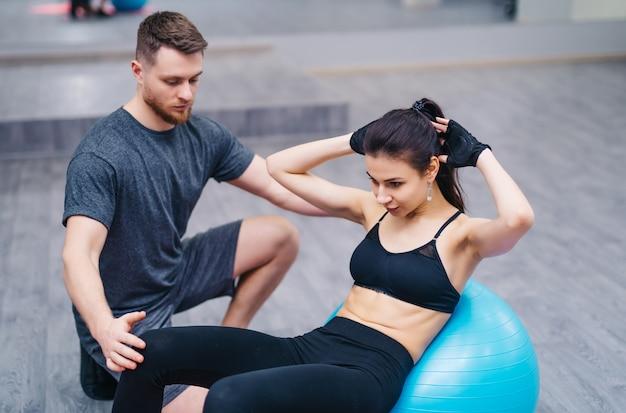 Mujer joven atractiva que hace los abdominales en una bola de la aptitud con el entrenador personal en el piso en gimnasio.