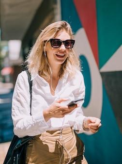 Una mujer joven atractiva que lleva gafas de sol usando el teléfono celular en luz del sol
