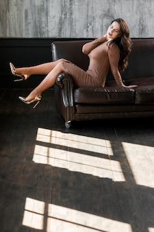 Mujer joven atractiva que lleva los tacones altos de oro que se sientan en el sofá
