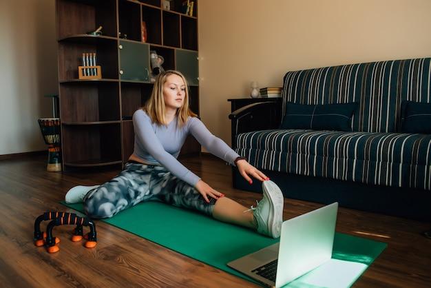 Mujer joven atractiva que mira la clase de entrenamiento en línea en la computadora portátil y que hace ejercicios de estiramiento en la estera en casa