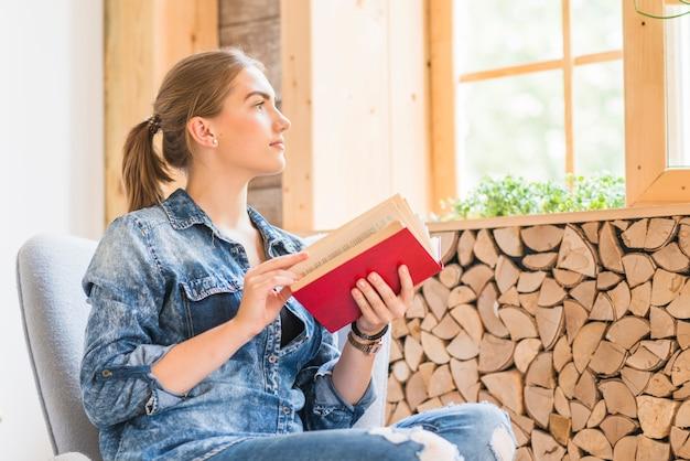 Mujer joven atractiva que mira la ventana con el libro que se sostiene