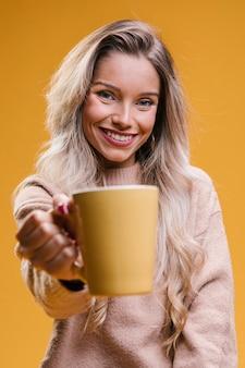 Mujer joven atractiva que muestra la taza de café que mira la cámara