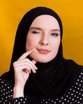 Mujer joven atractiva que parpadea su ojo mientras piensa sobre la superficie