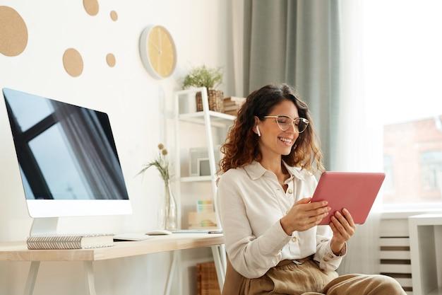 Mujer joven atractiva que participa en una conferencia en línea mientras se queda en casa