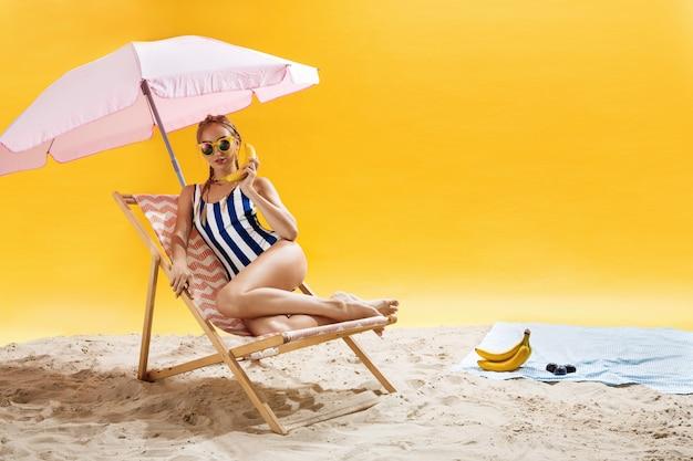 Mujer joven atractiva que presenta en la silla de playa rosada que se ríe
