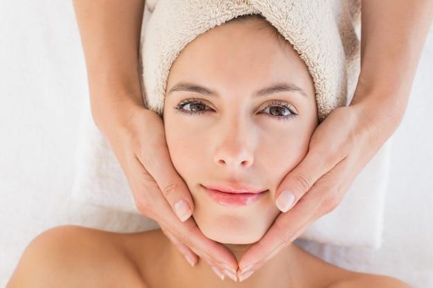 Mujer joven atractiva que recibe masaje facial en el centro de spa