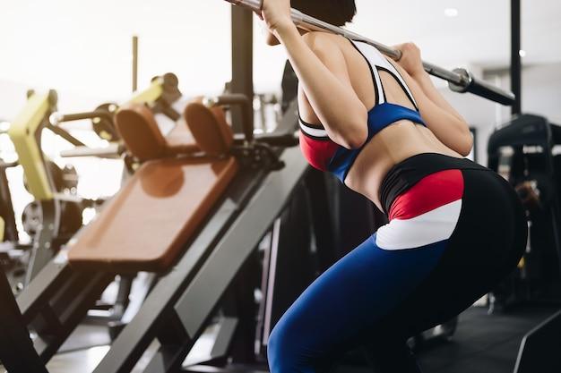 Mujer joven atractiva que se resuelve con la barra. chica de fitness sexy.