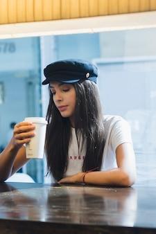 Una mujer joven atractiva que se sienta en el café que mira la taza de café para llevar a disposición