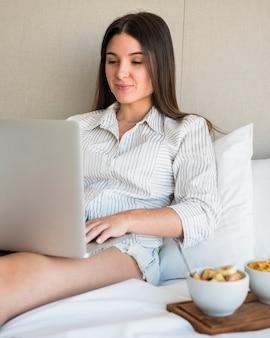 Una mujer joven atractiva que se sienta en cama usando la computadora portátil