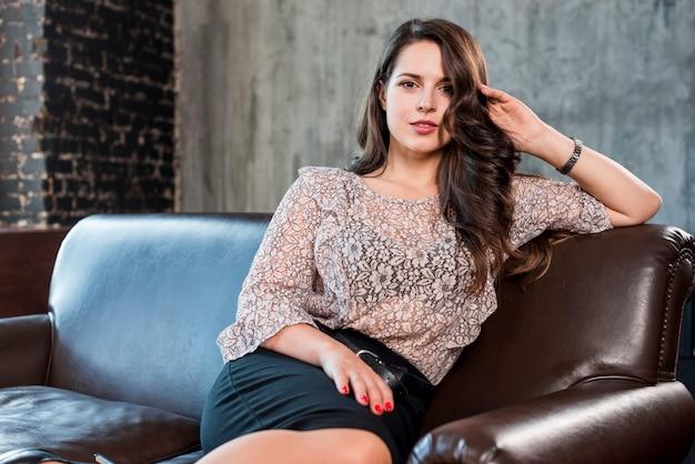 Una mujer joven atractiva que se sienta en el sofá que mira la cámara