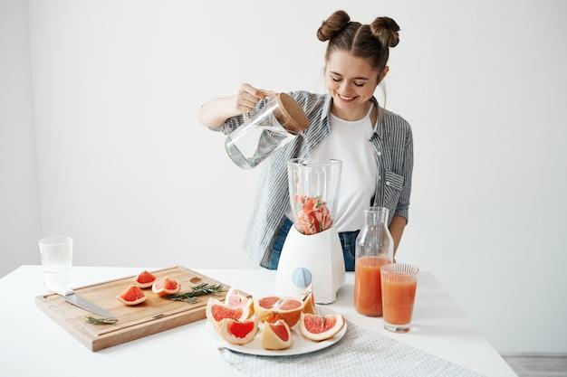 Mujer joven atractiva que sonríe agregando agua en licuadora con los pedazos de pomelo y el romero. dieta saludable alimentación nutrición.