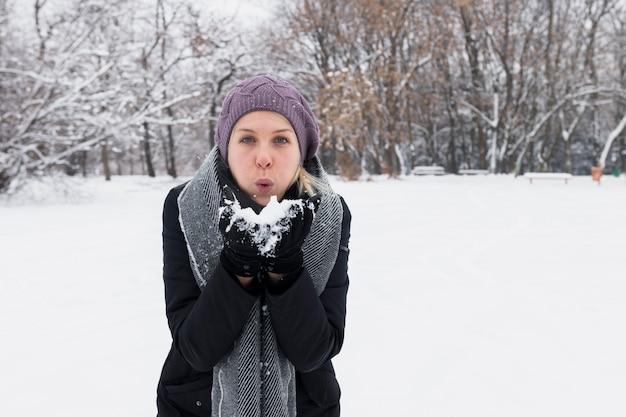 Mujer joven atractiva que sopla nieve en naturaleza del invierno