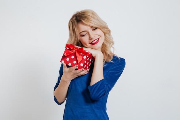 Mujer joven atractiva que sostiene la caja de regalo sobre la pared blanca