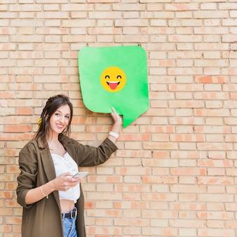 Mujer joven atractiva que sostiene el teléfono móvil y el mensaje emoji feliz contra la pared de ladrillo