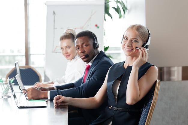 Mujer joven atractiva que trabaja en un centro de llamadas con sus colegas