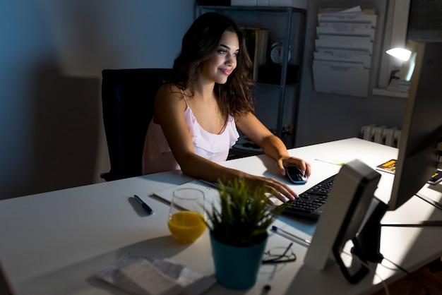 Mujer joven atractiva que trabaja en oficina del coworking en la noche. chica usando escritorio contemporáneo