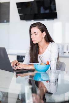 Mujer joven atractiva que usa la computadora portátil en el desayuno y sentándose en la cocina.