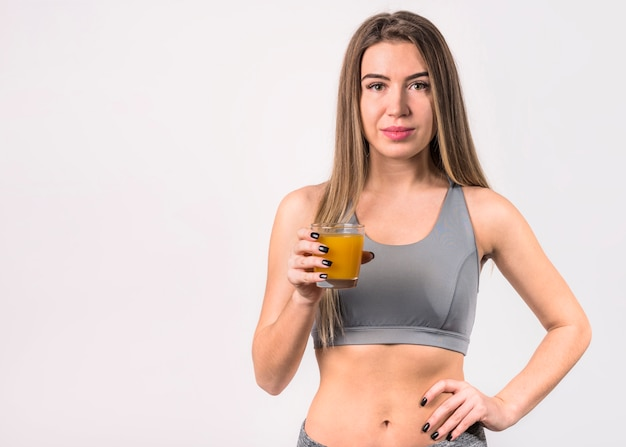 Mujer joven atractiva en ropa deportiva con vaso de jugo