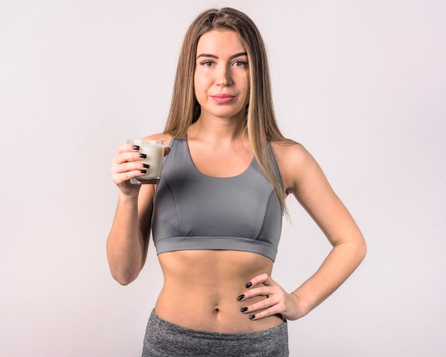 Mujer joven atractiva en ropa deportiva con vaso de leche