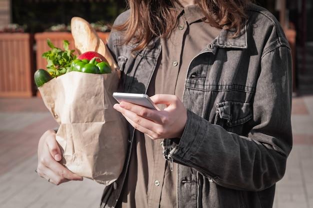 Mujer joven atractiva en ropa de estilo casual con bolsa de papel reciclable de comestibles comprados en la tienda local de verduras y comestibles o mercado.