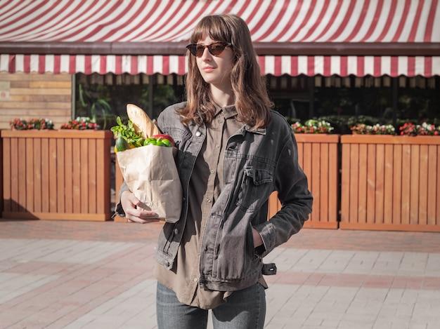Mujer joven atractiva en ropa de estilo casual con comestibles comprados en la tienda local de verduras y abarrotes o mercado.
