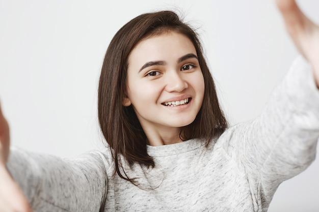 Mujer joven atractiva sincera sonríe ampliamente y estira las manos