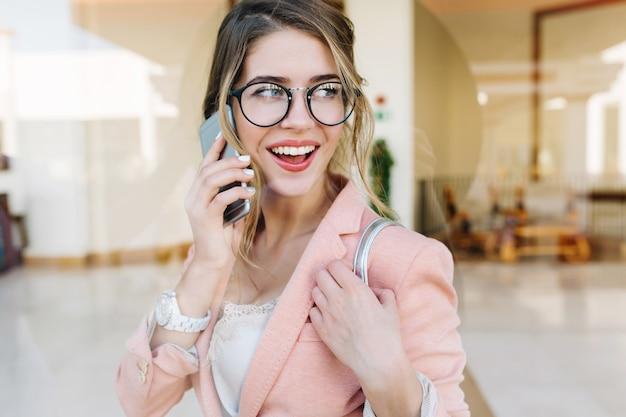 Mujer joven atractiva sonriendo y hablando por teléfono, mirando hacia un lado, de pie en el pasillo. ella tiene manicura corta blanca, relojes en su muñeca. vistiendo elegante chaqueta rosa.