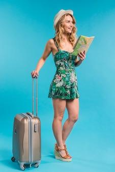Mujer joven atractiva sonriente en el mapa y la maleta de la tenencia del sombrero