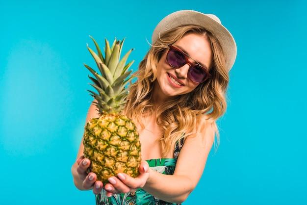 Mujer joven atractiva sonriente en el sombrero y las gafas de sol que sostienen la piña fresca