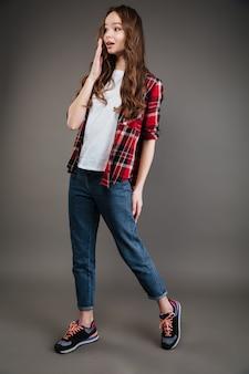 Mujer joven atractiva sorprendida en camisa a cuadros y jeans caminando