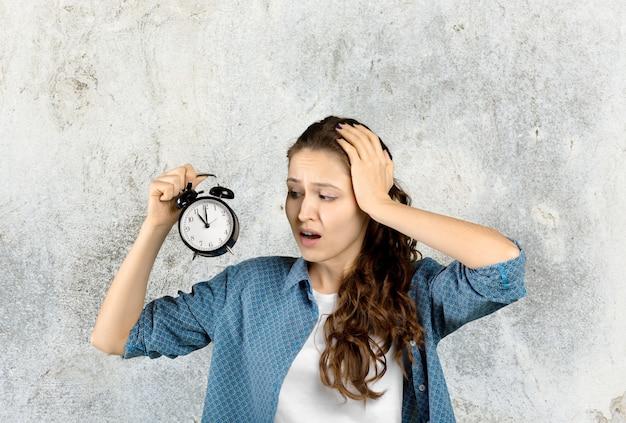 Mujer joven atractiva sorprendida que sostiene el despertador