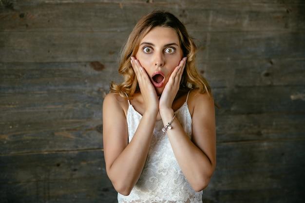 Mujer joven atractiva sorprendida sorprendida sobre algo, manteniendo la boca abierta
