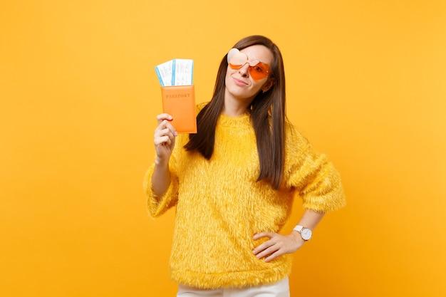 Mujer joven atractiva en suéter de piel, anteojos de corazón naranja con pasaporte y boletos de tarjeta de embarque aislados sobre fondo amarillo brillante. personas sinceras emociones, estilo de vida. área de publicidad.