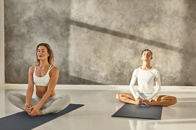 Mujer joven atractiva en sujetador deportivo y leggings practicando en la estera con su instructor masculino. dos principiantes y profesionales yoguis haciendo la misma pose de baddha kobasana en el gimnasio, estirando las piernas