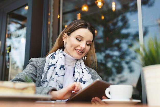 Mujer joven atractiva con tableta en café