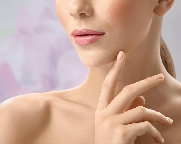 Mujer joven atractiva tocando su cara sensualmente