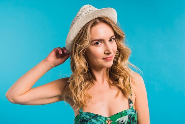Mujer joven atractiva en vestido y sombrero florecidos