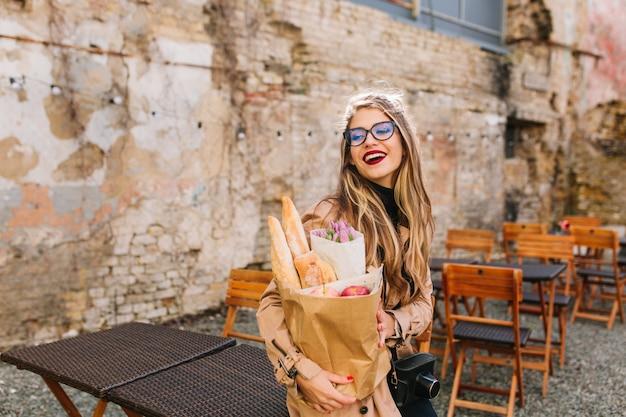 Mujer joven atractiva vino al café al aire libre después de comprar comida y mira hacia otro lado. chica rubia con estilo en vasos grandes posando delante de la pared vieja con bolsa de panadería y ramo de flores púrpuras.