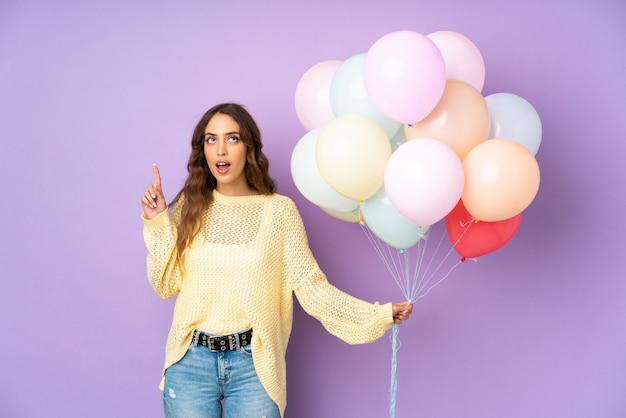 Mujer joven atrapando muchos globos en la pared púrpura señalando con el dedo índice una gran idea