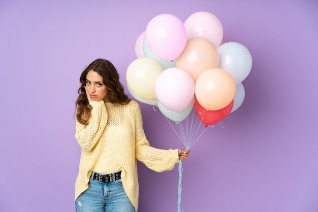 Mujer joven atrapando muchos globos sobre pared púrpura infeliz y frustrada