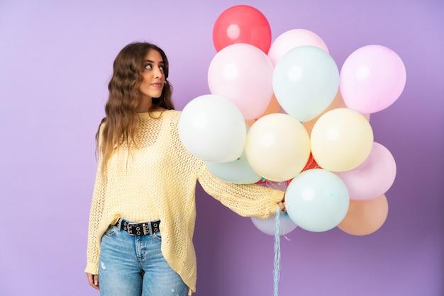 Mujer joven atrapando muchos globos sobre pared púrpura