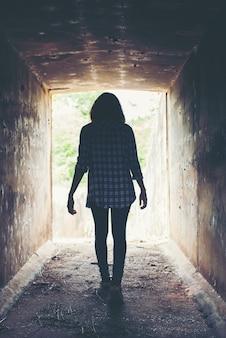 Mujer joven atravesando un túnel solitario