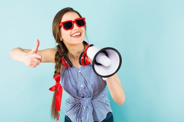Mujer joven con auriculares y altavoz