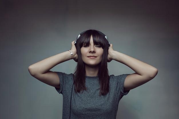 Mujer joven con auriculares en la pared