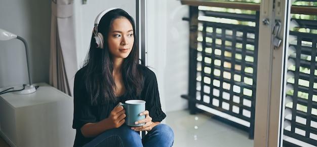 Una mujer joven con los auriculares sostiene una taza de café mientras está sentada en el dormitorio.