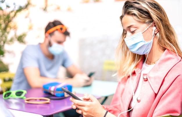 Mujer joven con auriculares usando la aplicación de seguimiento en teléfonos inteligentes móviles