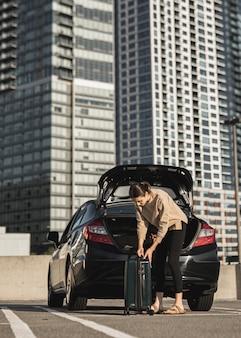 Mujer joven con un auto y una maleta