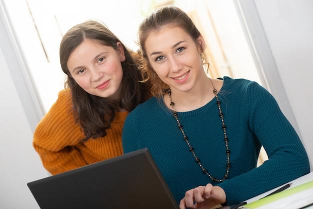 Mujer joven ayuda a una muchacha adolescente con la tarea