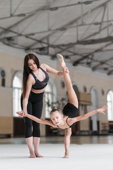 Mujer joven ayudando a la chica bailarina en la clase de baile